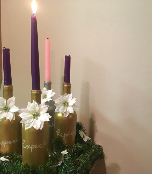 4 gold painted wine bottles and a silver one holding purple and pink candles